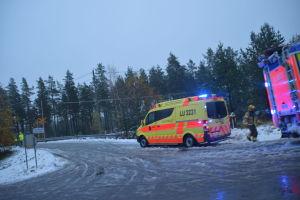 En ambulans står vid en snöig plankorsning. På bilden syns också flera brandmän.