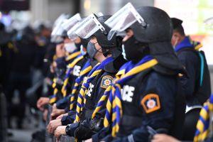 Thailändska poliser på rad med skyddsvisir.