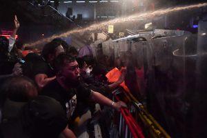 Thailändska aktivister besprutas med vatten.