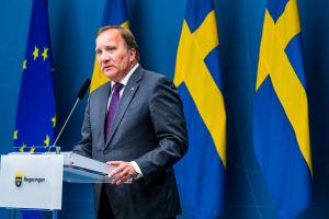 Stefan Löfven på pressträff framför EU-flagga och flera Sverigeflaggor.