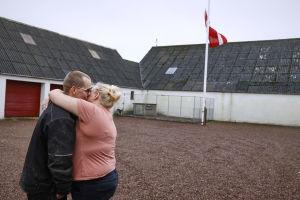 Minkfarmarna Peter och Trine Brinkmann Nielsen håller om varandra efter att ha hissat danska flaggan på halvstång på sin minkfarm i Boerglum Kloster på Jylland.