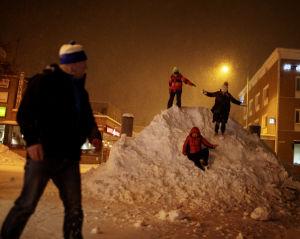 Turistit ilakoivat lumikasoissa.