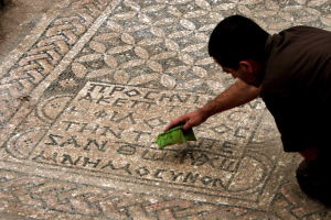 Mies tutkii ja puhdistaa vanhaa kreikkalaista tekstiä, joka on kivessä.