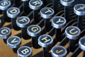 vanhan kirjoituskoneen kirjaimia lähikuvassa