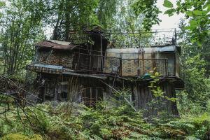 Fallfärdigt ruckel mitt i skogen: på taket en takterrass med stängsel runt.