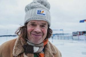 """Äldre man klädd i vinterkappa, randig halsduk och mössa med texten """"Finland Ice Marathon"""" i vintrigt landskap."""