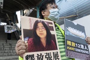 En man håller upp ett plakat med bild på en svarthårig kvinna och kinesiska tecken.