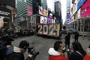 Fotografer omger en skylt av ledlampor som bildar siffrorna 2021.