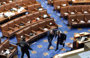 Kongressledamöter flyr undan oroligheter under kongressens session som avbröts av Trumpanhängare den 6 januari 2021 i Washington.