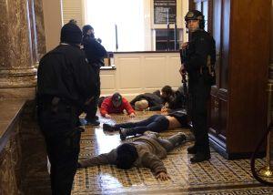 Demonstranter ligger på golvet med polis som övervakar.