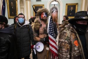Man med horn håller i amerikansk flagga.