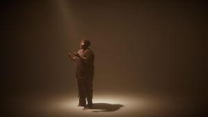 Rap-lupaus Hassan Maikal seisoo tyhjässä huoneessa valokeilassa