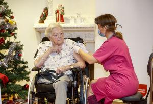 Äldre kvinna i rullstol får vaccin i armen av vårdpersonal med munskydd och visir.