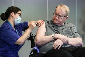 Man på servicehem får vaccin i armen av vårdpersonal med munskydd.