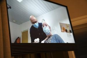 Bild på en skärm där en kvinna vaccineras.