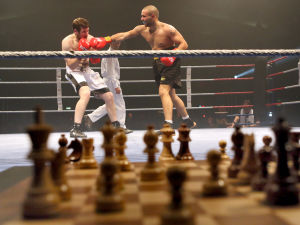 Etualalla shakkilauta epäskarppina, taustalla nyrkkeliyottelu