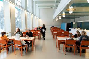 Paimion parantolan ruokasalissa. Plydissä on perheitä ruokailemassa ja kaukana tilan takaosassa istuu arkkitehti Henna Helander.