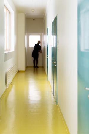 Paimion parantolan käytävä on pitkä ja lattia kirkkaan keltainen. Ovet ovat vihertävän siniset. Taustalla näkyy sumeana, miten Henna Helander avaa ovea seuraavaan käytävään.