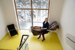 Arkkitehti Henna Helander istuu vanhanaikaisessa lepotuolissa parantolan porrastasanteella ja ihailee ikkunan takana kasvavaa mäntymetsää. Lattia on kirkkaan keltainen ja Helanderilla yllään sininen mekko.