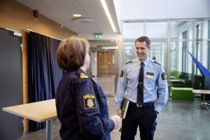 Två poliser i uniform, en kvinna och en man, pratar med varandra i kontorsliknande lokal.