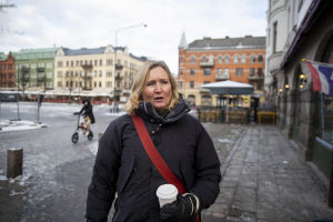 Kvinna med take away-mugg på Möllevångstorget i Malmö.
