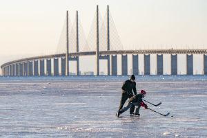 Man och barn spelar hockey på havsisen, med Öresundsbron i bakgrunden.
