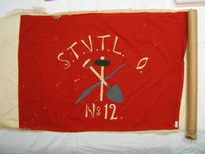 Punainen lippu, jossa kuvattuna lapio, poramoukari ja rautakanki, sekä kirjaimet STVL ja numero 12.