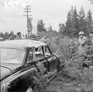 Lääninkomissaari tutkimassa varkaan kolaroimaa autoa 1957.