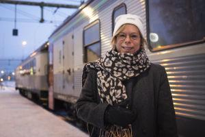 Kvinna står utanför ett tåg.