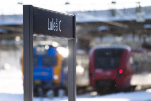 """Tågstationsskylt det står """"Luleå"""" på, och tåg i bakgrunden."""