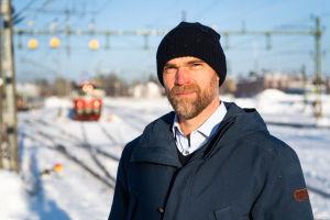 Man står framför tågdepå med tåg och spår i bakgrunden.