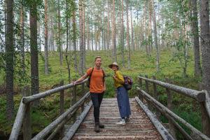Egenlandin juontajat Hannamari Hoikkala ja Nicke Aldén seisovat puisella sillalla. Taustalla kangasmetsää.