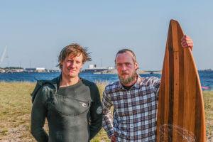 Mikael Hyryläinen ja Joachim Lindholm seisovat vierekkäin Tulliniemen rannalla. Joachimin vieressä puusta on tehty lainelauta.