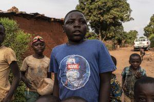 DieuDonné, klädd i en blå tröja med Marvel-logga, går längs en grusväg. Flera andra barn går runt honom.