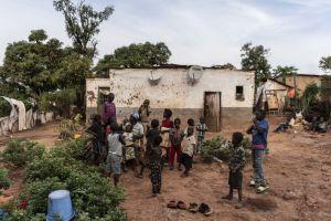 En massa barn framför ett anspråkslöst hus.