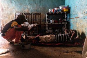 Gaspard Nombi ligger på golvet och får sitt brutna ben omvårdat av en man. Han bröt benet när han föll ner i en tunnel.