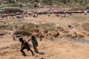 Pojkar går längs gruvsluttning. Lägre ner syns tält och fler människor.