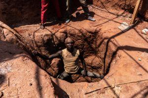 En man klättrar ner i ett gruvhål.