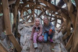 Tytöt Nellie ja Mea Wallden istuvat puusta tehdyn, pesää muistuttavan taideteoksen sisällä.