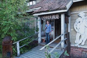 Vihreä vanha puutalo ulkoa, oven päällä tekstikyltti, talon vetäjä Olli Soini seisoo oven edessä kahvikuppi kädessä.