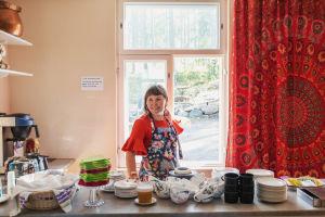 Keramiikkataiteilija Anni Paunila kahvilan tiskin takana yllään esiliina. Taustalla ikkuna, josta näkyy pihalle.