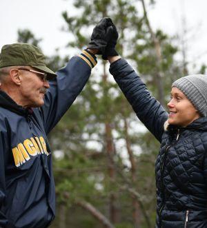 Veikko och Laura Salminen håller varandra i hand ute i naturen.
