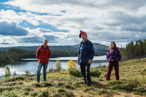 Tre personer står på en äng, i bakgrunden flyter en älv. Till vänster en man i röd jacka, i mitten en man i samisk hatt, till höger en kvinna i lila anorak.
