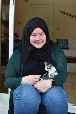 Marina Lischi istuu kissanpentu sylissään.