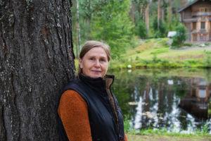 Puutaiteilija Natalia Podkolzina nojaa puunrunkoon. Taustalla näkyy lampi ja osa hirsitaloa.