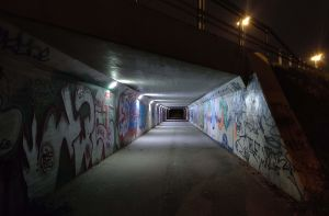 Hämärä alikulkutunneli, jonka seinillä graffiteja