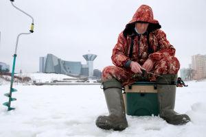Vanha mies pilkkii jäällä, joella, taustalla on rakennuksia.