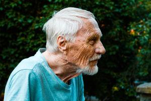 Vanhan ryppyisen ja kumaran miehen sivuprofiili