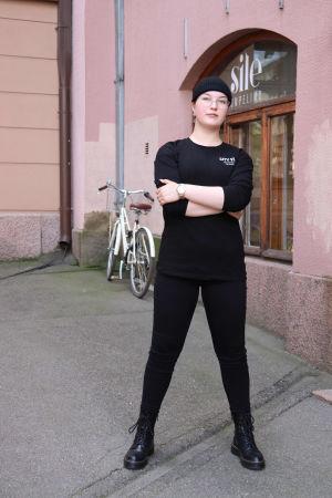 Nuori nainen seisoo kadulla kädet puuskassa