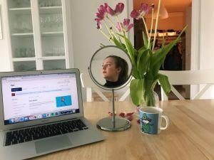 Pöydällä tietokone, jonka vieressä meikkipeili josta kuvastuu nuoren naisen kasvot.